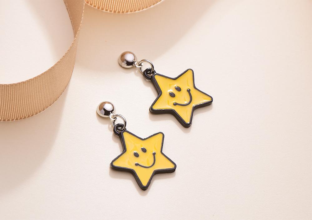 亮眼黃色笑臉星星 黏式耳環,桌上展示。