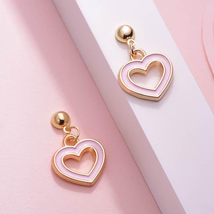 清新簍空粉嫩愛心 黏式耳環,桌上展示。