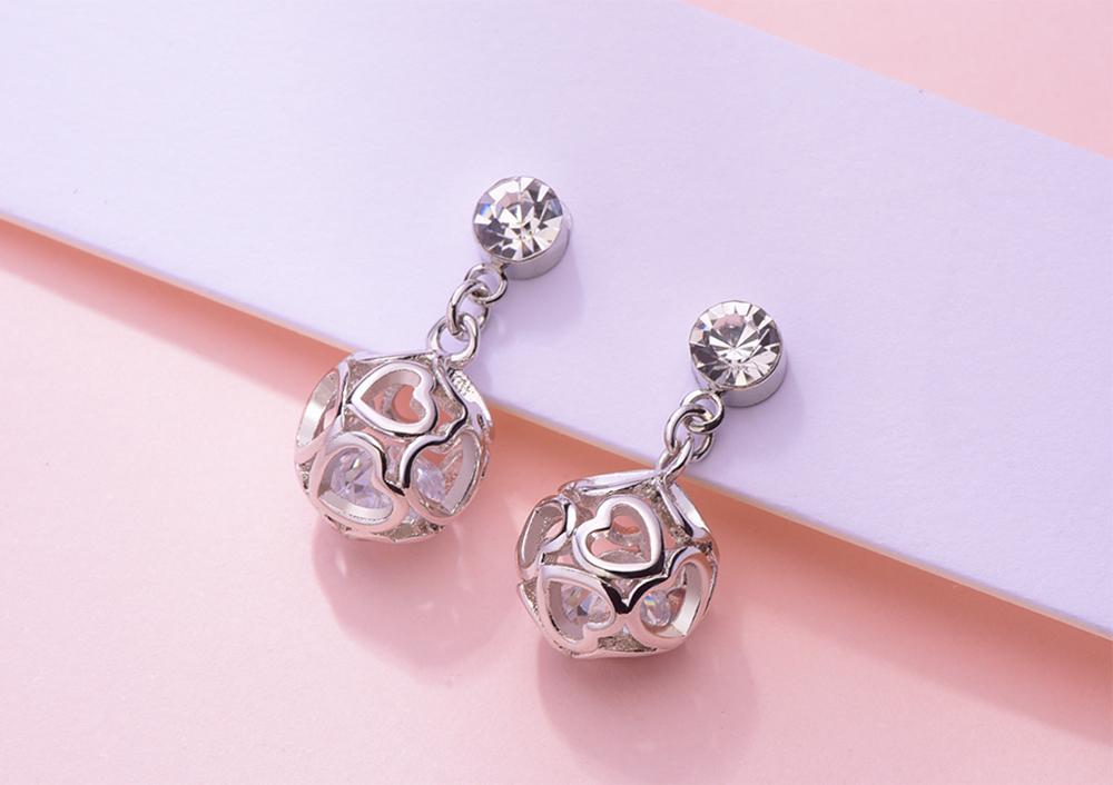簍空愛心圓球 耳針/黏式耳環,桌上展示。