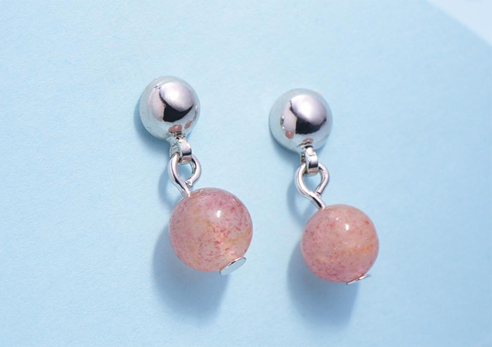 迷你簡約粉嫩水晶 耳針/黏式耳環,桌上展示。
