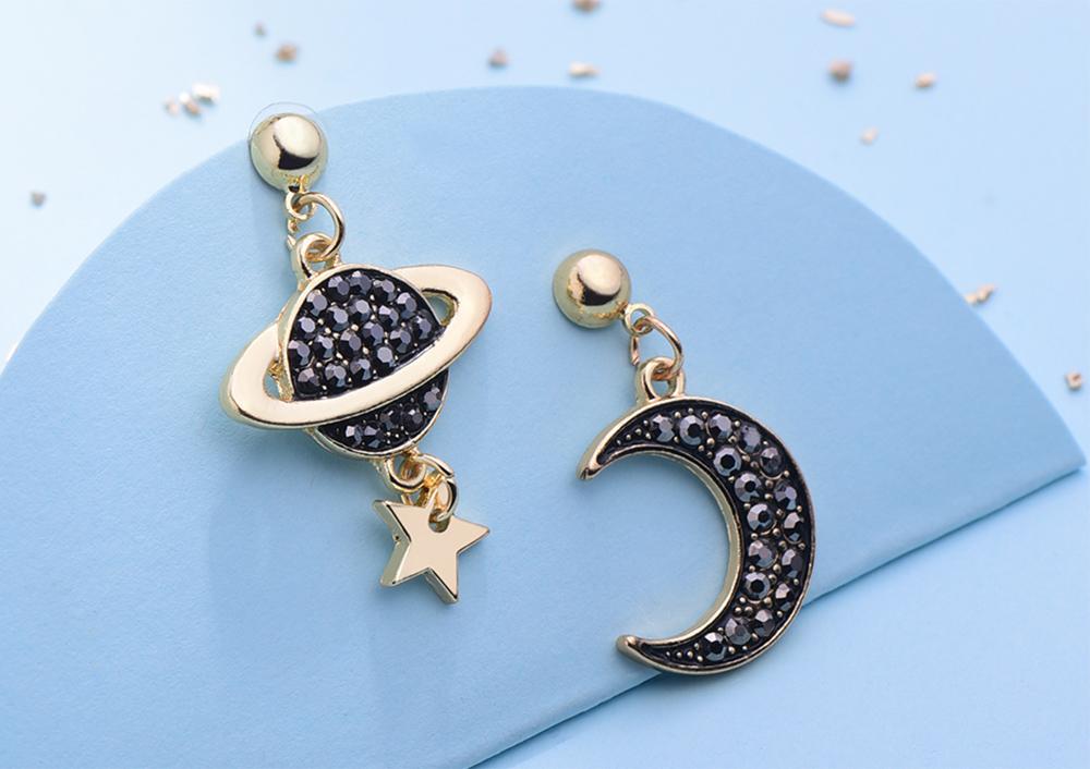 耀眼月亮宇宙星星 黏式耳環,桌上展示。