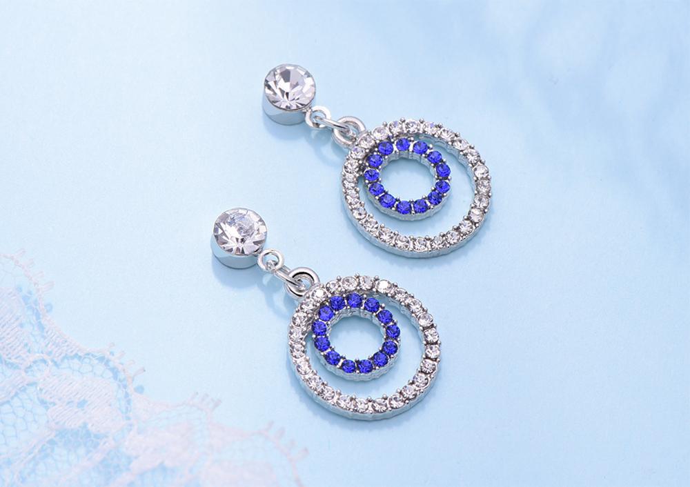 簍空雙圓鑲鑽 耳針/黏式耳環,桌上展示。