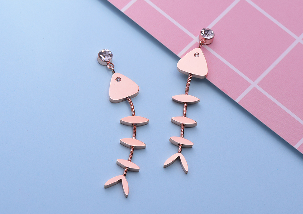 個性萌趣小魚骨頭 耳針/黏式耳環,桌上展示。