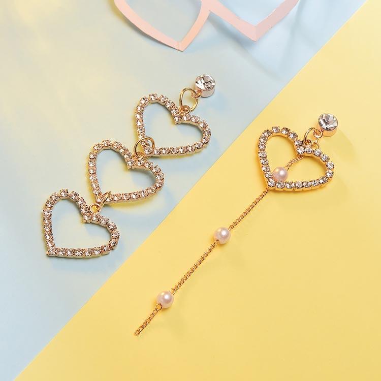 不對稱簍空愛心珍珠 耳針/黏式耳環,桌上展示。