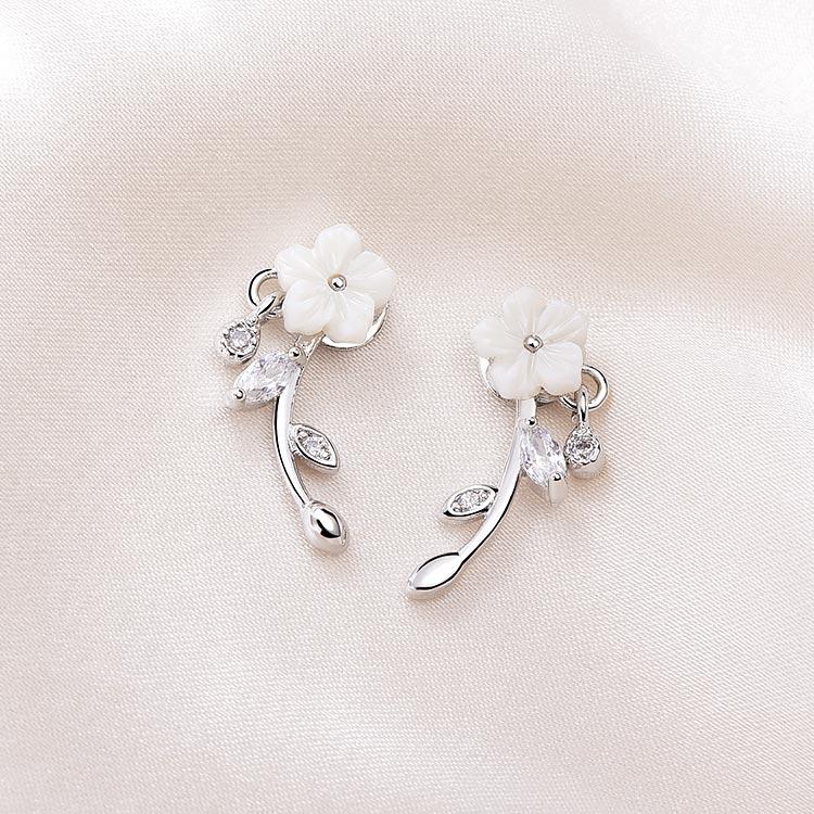優雅擺動雕刻梅花 黏式耳環,桌上展示。