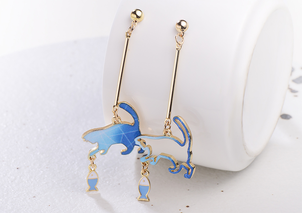 不對稱貓咪逗小魚 耳針/黏式耳環,桌上展示。