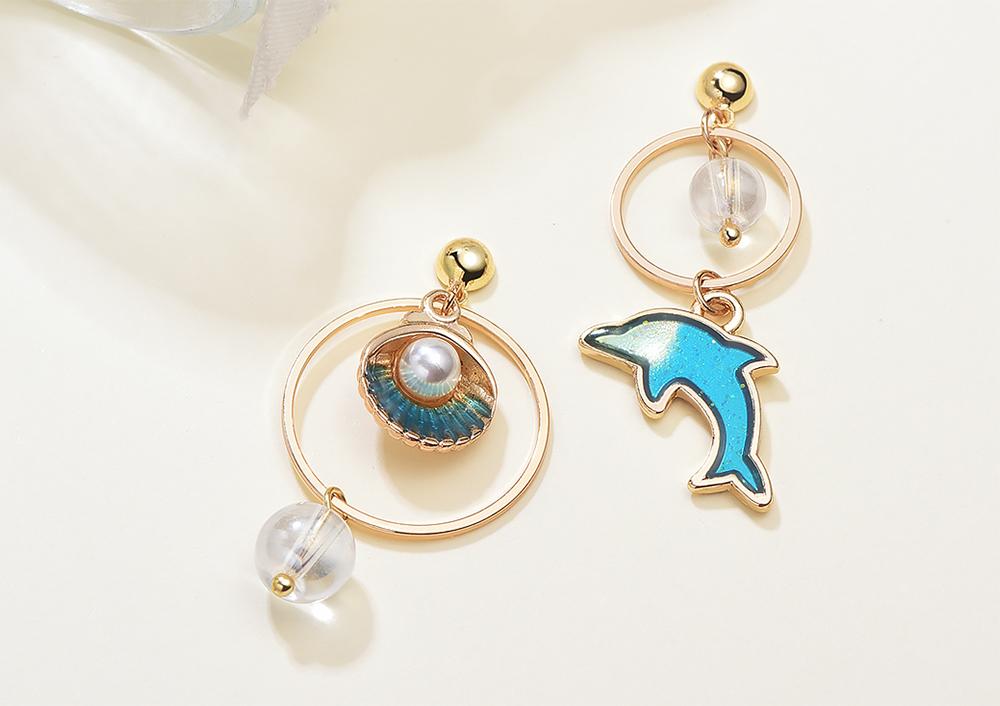不對稱海豚珍珠貝殼 耳針/黏式耳環,桌上展示。
