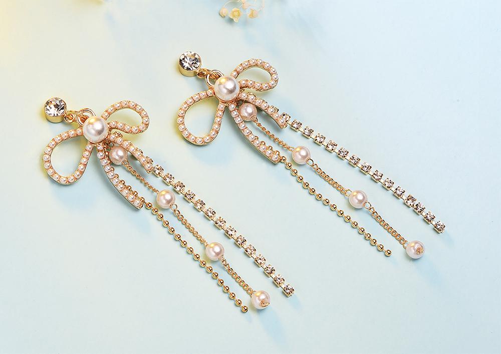 長款蝴蝶結鑲鑽流蘇 耳針/黏式耳環,桌上展示。