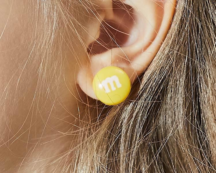 模特兒配戴展示:經典M字巧克力豆造型,可愛逗趣,輕巧時尚,創新的黏貼式耳環,不必擔心長時間配戴耳夾的不舒服感。