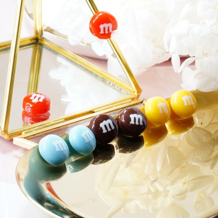 仿真M字巧克力豆 黏式耳環,桌上展示。