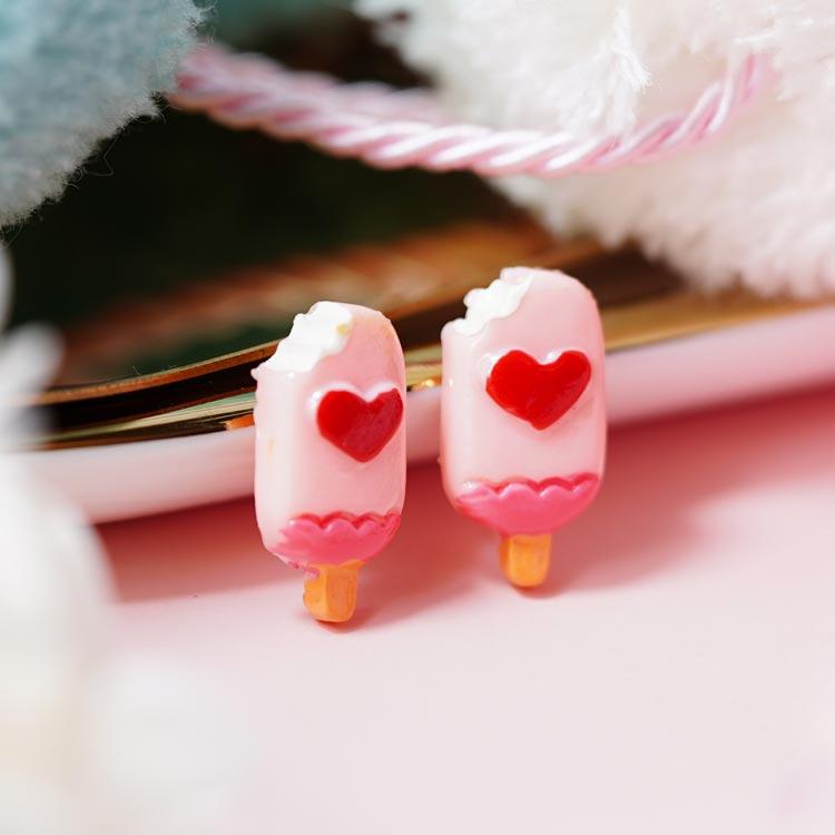粉嫩愛心草莓雪糕 黏式耳環,桌上展示。