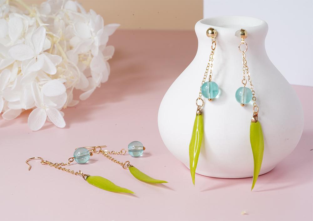 氣質珍珠鑲鑽毛球 黏式耳環,桌上展示。