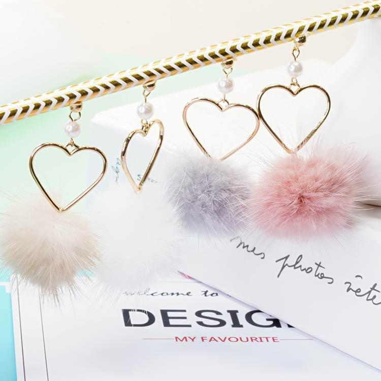 簍空愛心珍珠貂毛圓球 耳針/黏式耳環,桌上展示。