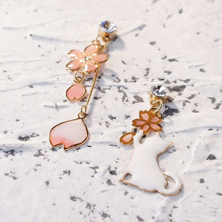 不對稱櫻花貓咪 耳針/無耳洞黏貼式耳環,桌上展示。