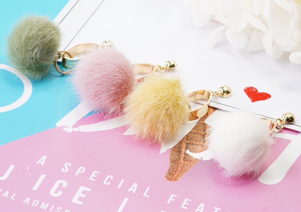 甜美糖果色圓環毛球 耳針/黏式耳環,桌上展示。