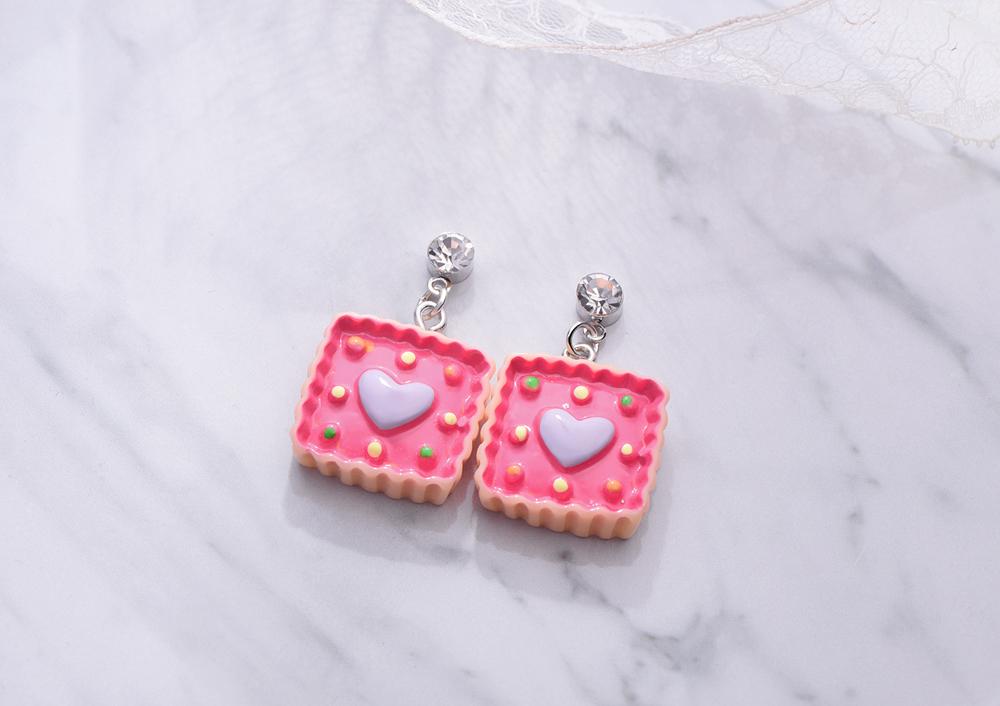 可愛點心派愛心黏式耳環,桌上展示。